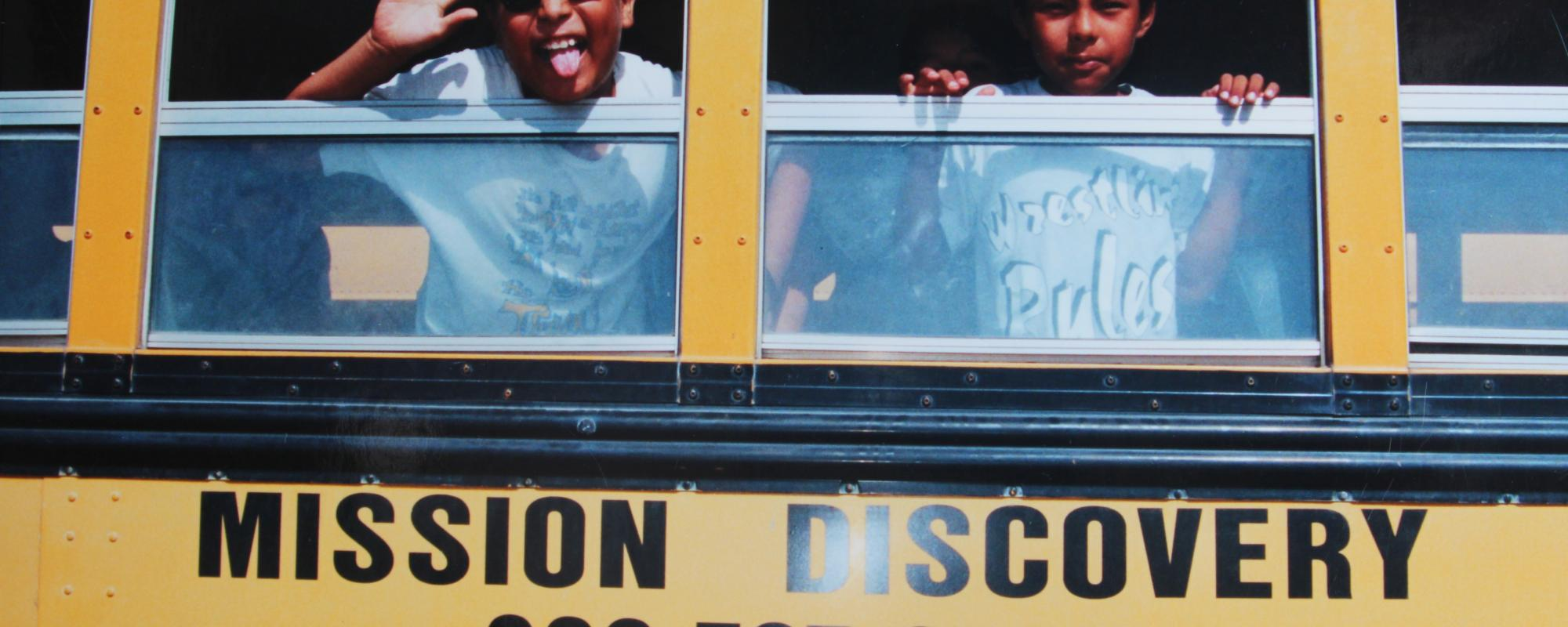 kids peaking out of a mission discovery school bus