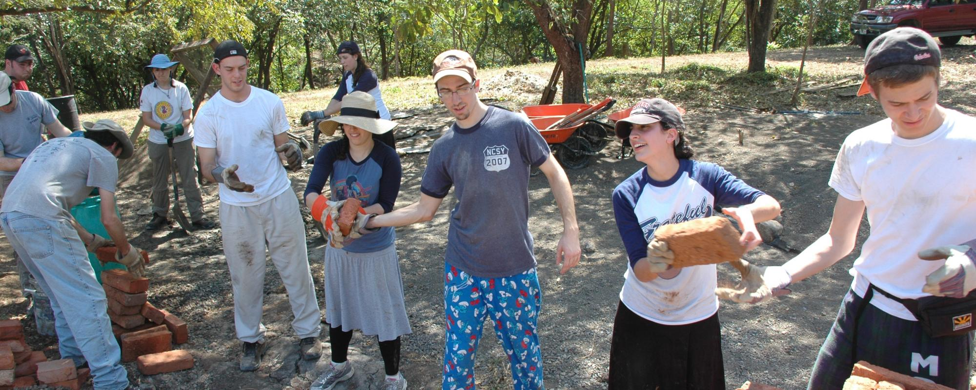 volunteers passing bricks