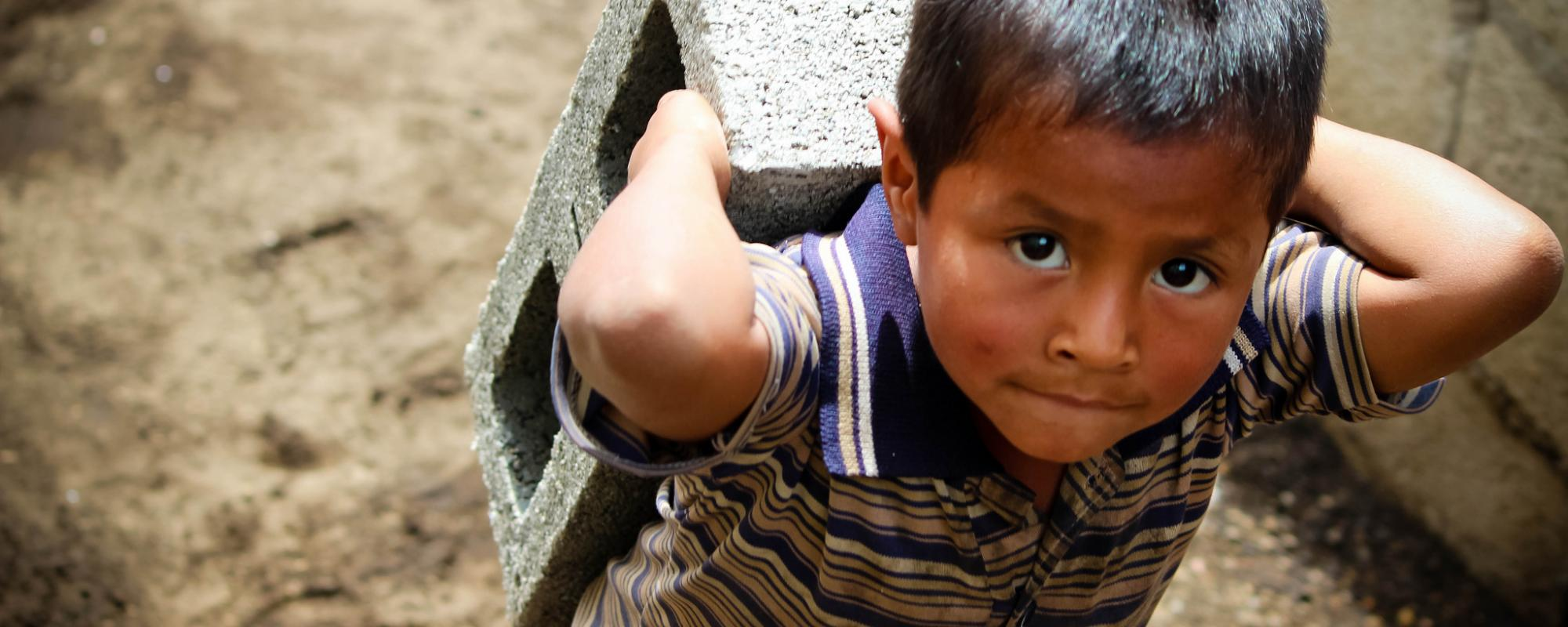 young child carrying a concrete block