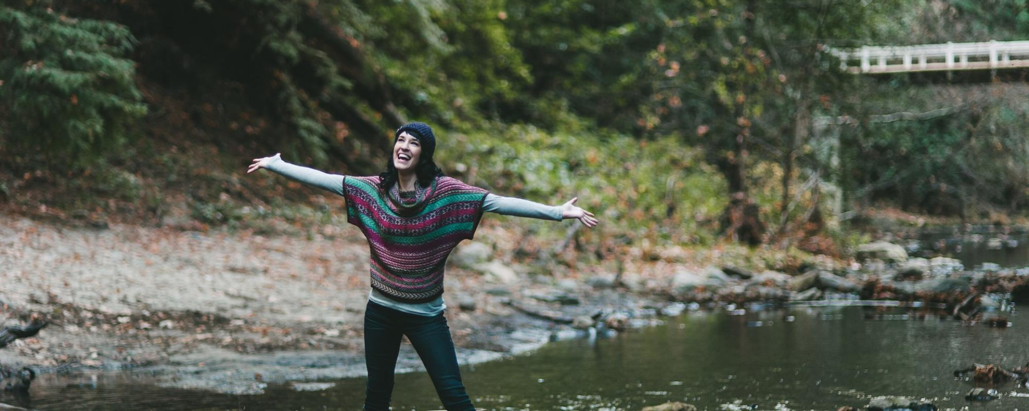 smiling woman in front of a stream of water