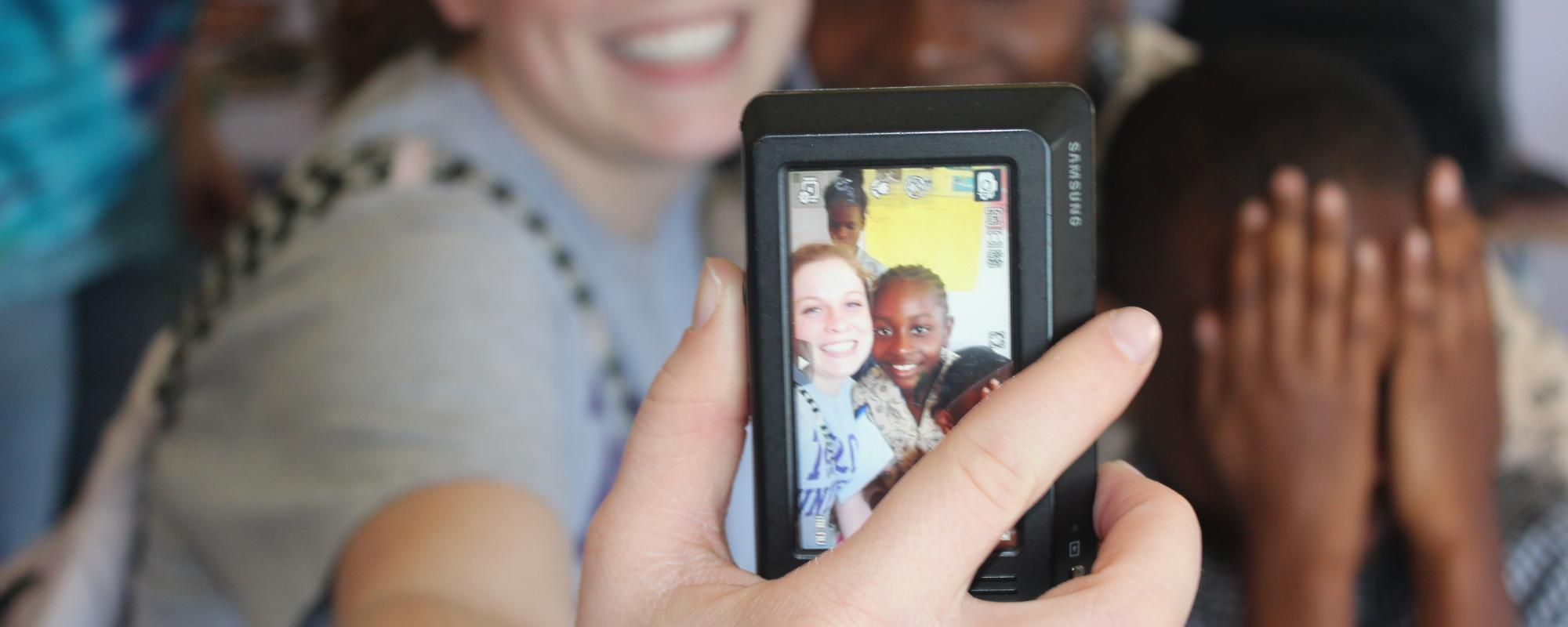 volunteers taking a selfie with a child