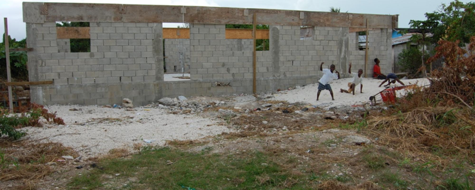 children happy in front of a work project for a building in progress