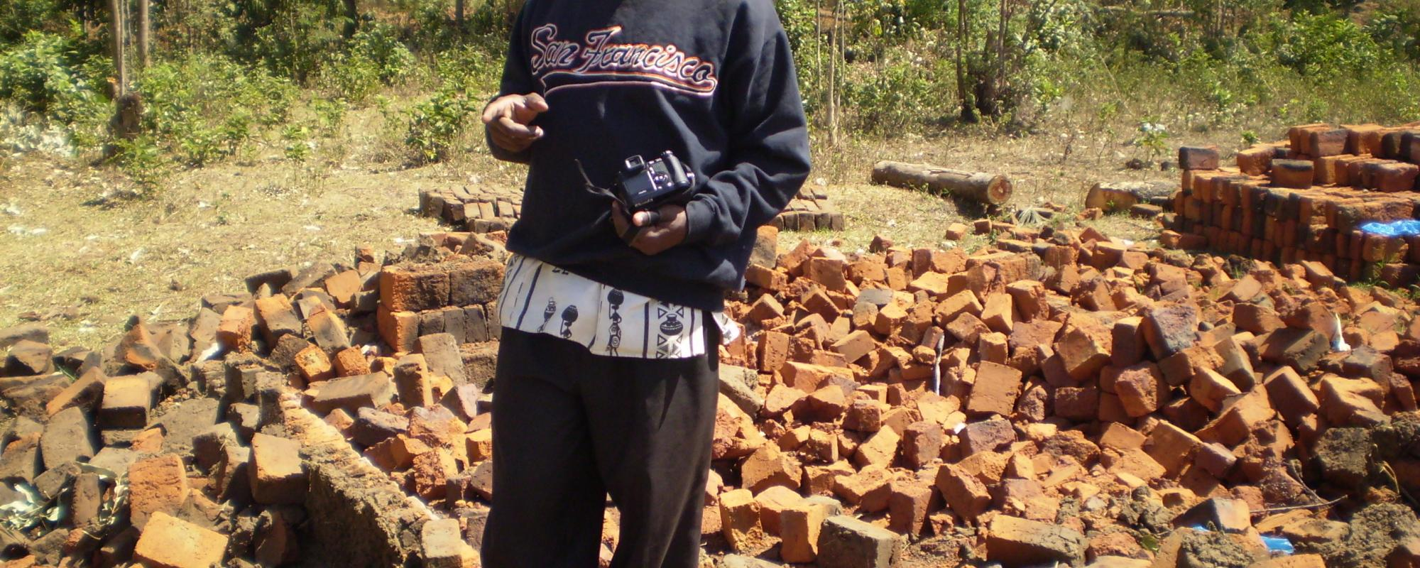man standing in front of piles of bricks